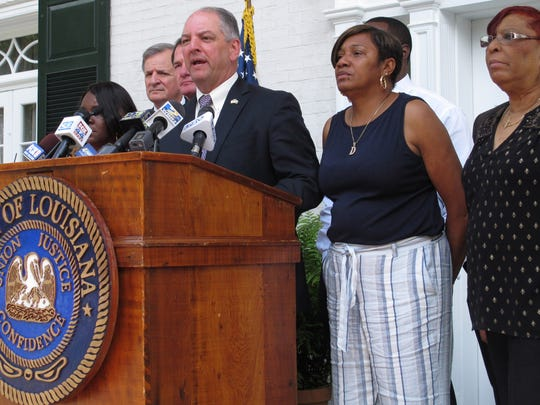 Gov. John Bel Edwards speaks at a podium with Baton