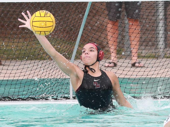 Mt Whitney's Hala Quinlan (1) blocks a Reedley shot in the Central Section Division III girls water polo championship game.