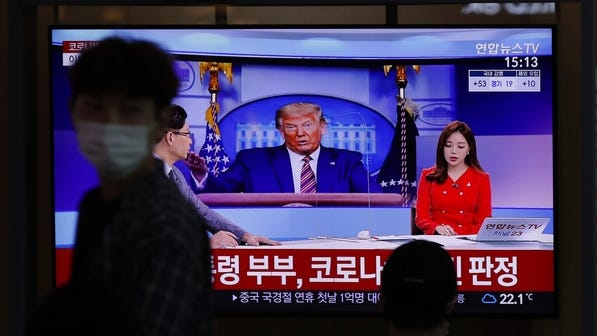 """A man wearing a face mask walks near a TV screen reporting about U.S. President Donald Trump and first lady Melania Trump during a news program with a file image of Trump at the Seoul Railway Station in Seoul, South Korea. Trump said early Friday that he and Melania Trump have tested positive for the coronavirus. The Korean letters read: """"President Donald Trump and first lady Melania Trump tested positive for COVID-19."""""""
