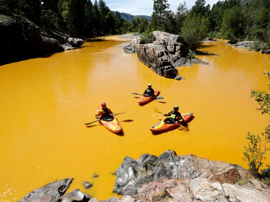 In this Aug. 6, 2015, photo, people kayak in the Animas River near Durango, Colo., in water colored from a mine waste spill. U.S. prosecutors have declined to pursue criminal charges against an employee of the Environmental Protection Agency over a massive mine wastewater spill that fouled rivers in three states, a federal watchdog agency said. The EPA's Office of Inspector General disclosed Wednesday, Oct. 12, 2016, that it recently presented evidence to prosecutors that the unnamed employee may have violated the Clean Water Act and given false statements.