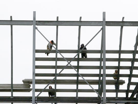 Workers on Tuesday disassembled grandstand seating at Dover International Speedway as part of the reduction in seating at the raceway to a capacity of 85,000.