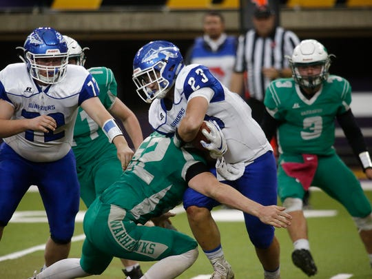 Rockford senior running back Kaden Lyman tries to fight through the tackle of Southeast Warren junior Bryce Vandelune. Southeast Warren lost 52-19 to Rockford in the 8-player class semifinals Nov. 8 at the UNI-Dome in Cedar Falls.