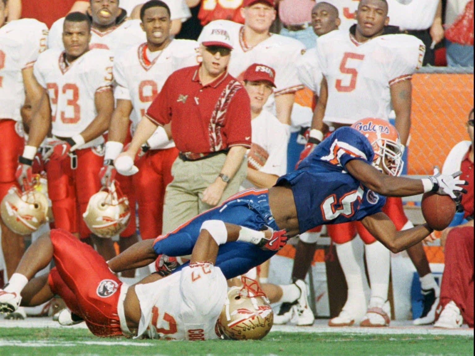 Florida wide receiver Jacquez Green (5) makes an acrobatic catch in front of Florida State's Tay Cody (27) and the Florida State bench during the Gator's 32-29 win on Nov. 22, 1997 in Gainesville.