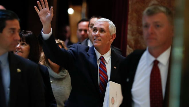 Vice President-elect Mike Pence waves as he arrives at Trump Tower.