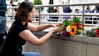 A woman puts down flowers near the mall where a shooting took place leaving nine people dead in Munich, Germany.
