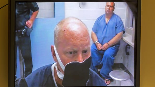An inmate, Robert Lee Carter, wears a mask as he appears remotely during a hearing in the first appearance courtroom Friday, April 24, 2020. The proceedings are now held by video, with inmates either in isolation, or a holding cell outside the courtroom.  Carter is charged with cocaine possession, multiple counts of aggravated battery, and contempt of court.