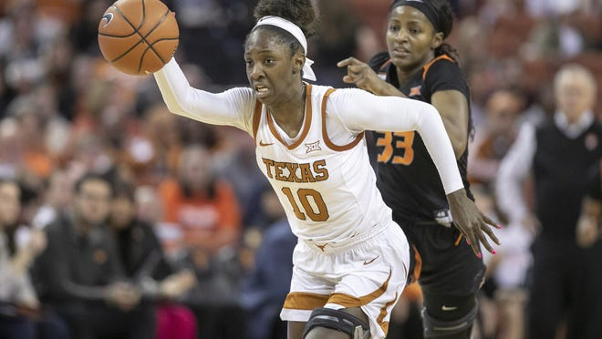 Texas guard Lashann Higgs dribbles the ball past Oklahoma State guard Clitan de Sousa in a game this past March. Higgs recently signed a contract with a professional women's basketball team in Spain.