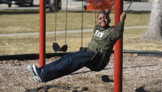 Mwangi Mumfield, 9, of Detroit, smiles as he swings on a record warm day at Palmer Park  on Saturday  February 18, 2017.