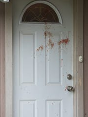 Blood on the door of the neighboring home where law enforcement are investigating a homicide on Aspen Drive in Portland on Tuesday, April 18, 2017.