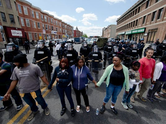 """People clasp hand and sing the hymn """"Amazing Grace"""" Tuesday, April 28, 2015, in Baltimore, in the aftermath of rioting following Monday's funeral for Freddie Gray, who died in police custody. The streets were largely calm in the morning and into the afternoon, but authorities remained on edge against the possibility of another outbreak of looting, vandalism and arson. (AP Photo/Matt Rourke)"""