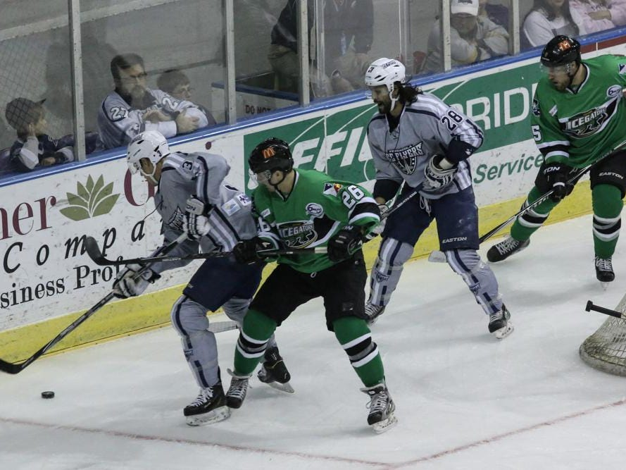 Ryan Kesti, left, of the Ice Flyers, works to keep the IceGators Brad Bourke from the puck during Friday night's game at the Pensacola Bay Center.