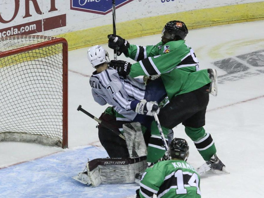 Alex Hudson, right, of the Louisiana IceGators, pushes Josh Cousineau, 7, of the Ice Flyers, over the IceGators goalie, Brad Barone, during Friday night's game at the Pensacola Bay Center. Hudson received an interference penalty due to this.