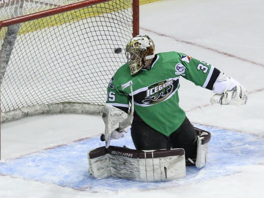 The IceGators goalie, Brad Barone, looks back as Ice Flyers Adam Pawlick's shot goes into the goal during Friday night's game at the Pensacola Bay Center.
