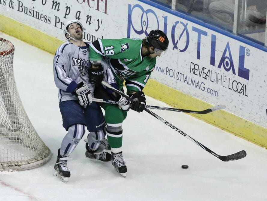 Josh Cousineau, left, of the Ice Flyers, falls back after getting hit with an elbow from Jake Hauswirth during Friday night's game at the Pensacola Bay Center.
