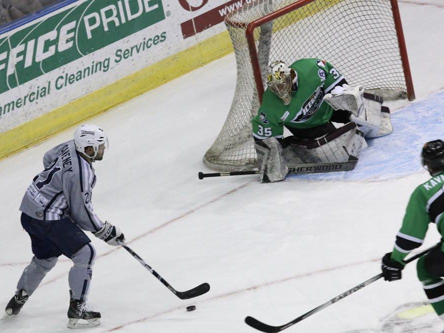 Joe Caveney, left, of the Pensacola Ice Flyers prepares to take a shot against the Louisiana IceGators goalie, Brad Barone, during Friday night's game at the Pensacola Bay Center.