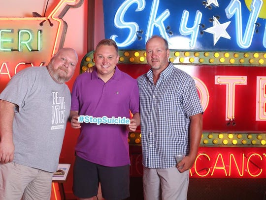 Rusty Lockett, event volunteer, left, with City of Cincinnati Councilman Chris Seelbach, middle, and partner Craig Schultz, right, at the Suicide is a Drag fundraiser held at the American Sign Museum.