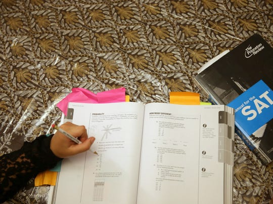 Suzane Nazir uses a Princeton Review SAT Preparation book to study for the 2014 test.