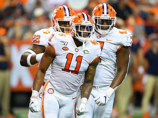 Sep 14, 2019; Syracuse, NY, USA; Clemson Tigers linebacker Isaiah Simmons (11) reacts to a defensive play with teammates defensive end Justin Mascoll (7) and defensive tackle Xavier Kelly (22) against the Syracuse Orange during the third quarter at the Carrier Dome. Mandatory Credit: Rich Barnes-USA TODAY Sports