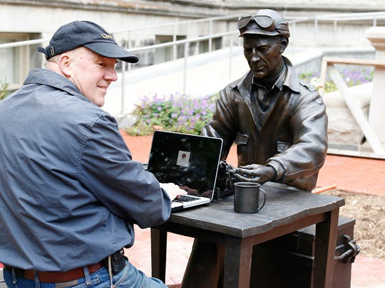 Sculptor Tuck Langland with his statue of Ernie Pyle outside Franklin Hall at Indiana University.