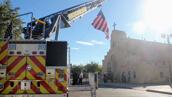 The American flag waves in front of Immaculate Conception Church from a Boles Acres firetruck. Law enforcement agencies and other first responders attended the second annual Blue Mass Thursday.
