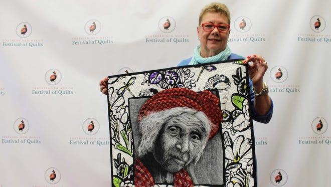 World renowned quilter, author and photographer Pam Holland shows off one of her artistic quilts Tuesday at First National Bank.