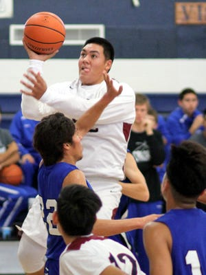 Senior Andres Villa elevates toward the basket and deposits two of his team-high 19 points in a losing effort against Carlsbad on Saturday afternoon at Deming High School. The eighth-ranked Cavemen took an 85-53 victory.