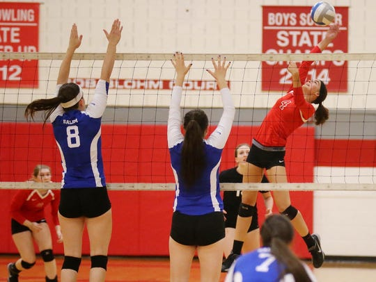 Canton's Emma Clark (No. 4) tries to power the ball
