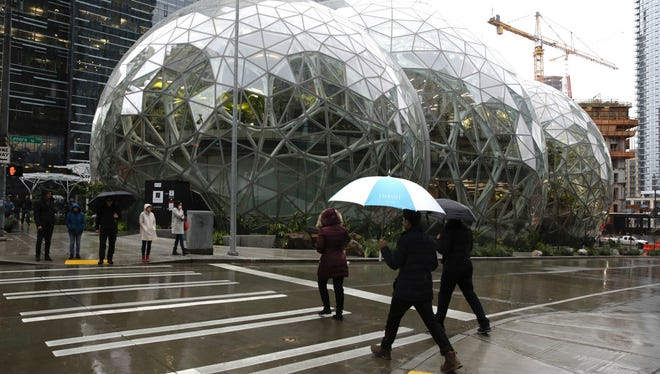 People walk past the Amazon Spheres, in Seattle, Wash. on Jan. 29, 2018, during the grand opening of the company's new office space. Amazon opened its new Seattle office space which looks more like a rainforest. The company created the Spheres Complex to help spark employee creativity.