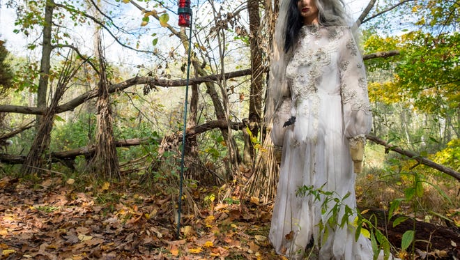 A mannequin dressed in a wedding dress next to one of the torches used to light the trail is one of the many scares people will find in the Haunted Forest at Panic at Pine Stump Hollow.