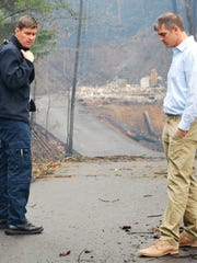 Pigeon Forge Fire Lt. Josh Carr, left and Eric Brackins, assistant city manager, assess the damage on Troy Drive in Pigeon Forge Tuesday, Nov. 29, 2016, after a wildfire ripped through the residential area Monday night, reducing homes and cabins to ruins.