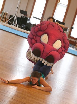 Katherine Marino, a member of PUSH Physical Theatre, gets dragged away and eaten by a large puppet creature operated by members of La Coperacha Puppet Co. as they move through a segment of the show during their rehearsal for their upcoming performance of Don't Blame Anyone.