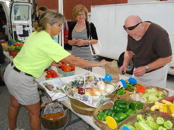 Marty Wood of Scott Farms sell produce to Tatiana and Patrick Nettles of Independence during the Independence Farmer's Market July 26.