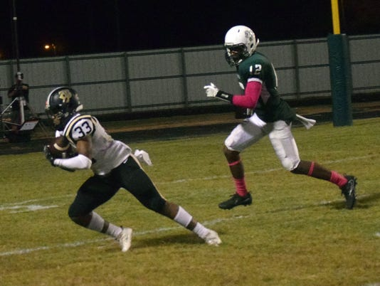 Jena High School's D.J. Major (33, left) intercepts a pass intended for Peabody Magnet High School's Thomas Miles (12, right).