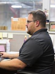 Greg Austin works at his desk at Spencer-based Protect
