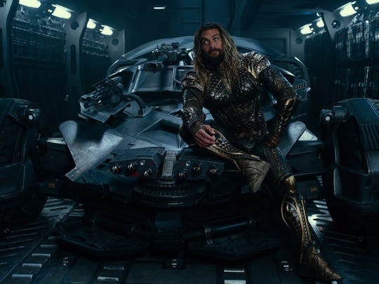 "Aquaman (Jason Momoa) chills on the Batmobile in ""Justice League."""