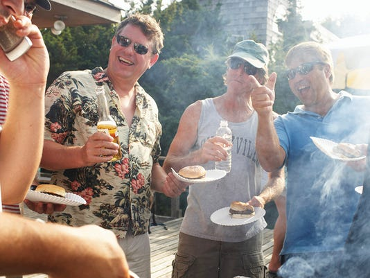 Man barbecuing using mobile phone, friends laughing in background