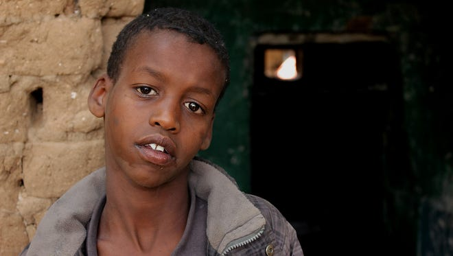 13-year-old Mohammed who lives on the streets of Hargeisa, stands outside the abandoned building where he sleeps with other homeless children and adults.