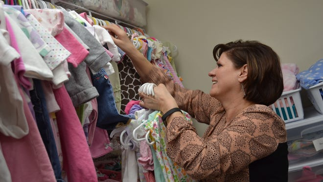 Toni Brubaker, executive director of  Heartbeat Hope Medical Pregnancy Center, hangs baby clothes that are given to clients seeking help with unplanned pregnancies.
