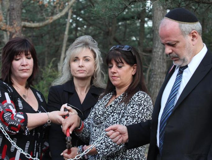 Janine Dalconzo, left, Susan Simms and Christine Volpe, along with Rabbi Jan Rosenberg, Beth Zion Messianic Synagogue, cut symbolic chain and offer prayer to break the cycle of fatal accidents and heroin overdoses in the area,  during  National Day of Prayer  in Jackson Thursday, May 1, 2014, Jackson.