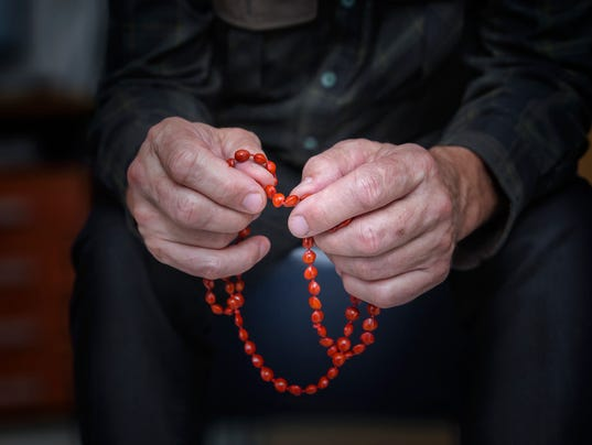 Close view of men's hands with rosary