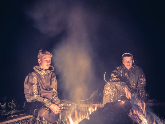 Teenagers boys in the camp by the fire in the night