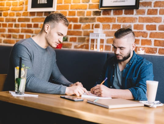 Two young men sitting in a cafe, discussing.