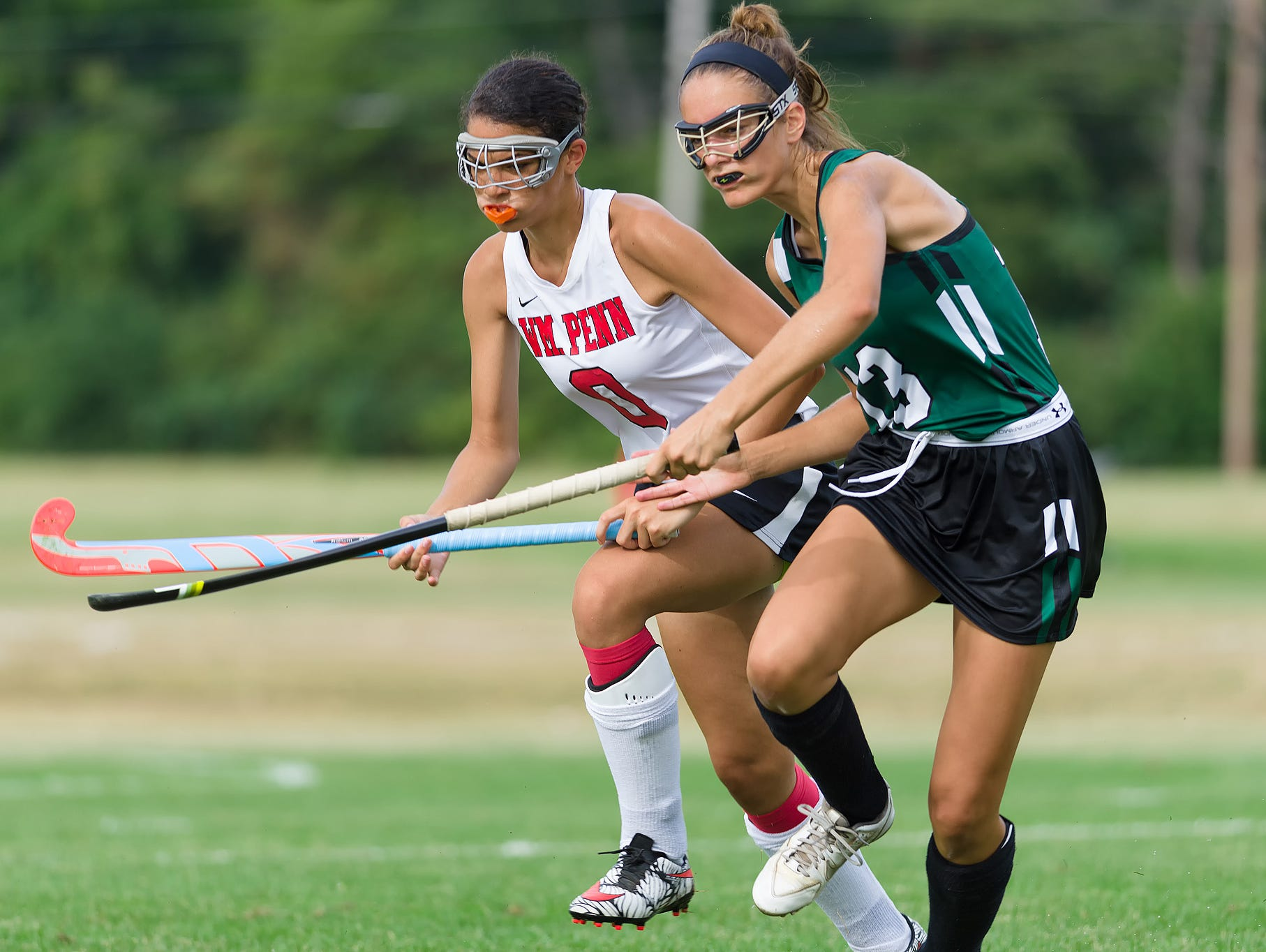 Elizabeth Soucy (13) of Mt. Pleasant and Makayla Robinson (0) of William Penn race for the ball in the William Penn vs Mt. Pleasant field hockey game at William Penn on Tuesday.