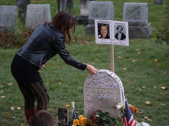 """Jillian Paris places an """"I Voted"""" sticker on the headstone of Susan B. Anthony on Nov. 8."""