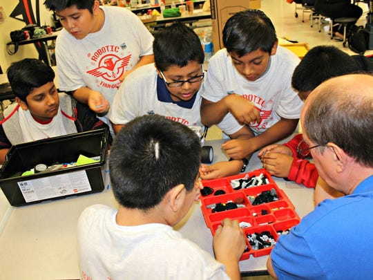 The EFMC Robotic Thunderbirds from Indiantown Middle School are pictured working with a volunteer mentor as they work to better their robot's performance.