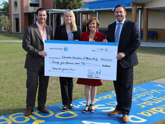 Kevin Staten, EFMC board president; Lisa Rhodes, EFMC executive director; Representative Gayle Harrell, EFMC board member; and Ian Cotner, EFMC board member and AT&T representative, accept a $25,000 grant from AT&T to assist with increasing graduation rates in Martin County.