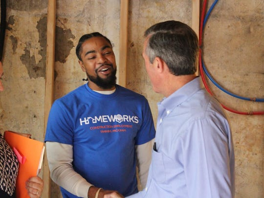 Kashif Handy greets Gov. John Carney during a tour of an Interfaith Community Housing of Delaware site in October 2017. Handy said Interfaith instructed him to act out construction tasks in an attempt to curry favor with the governor. The site was not actually under active construction at that time.