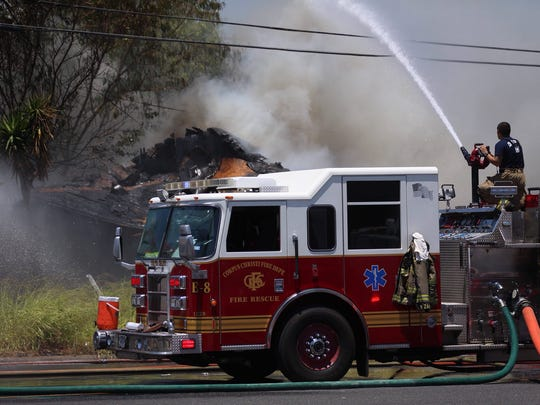 Corpus Christi Fire Department crews work to put out a blaze Thursday, May 17, 2018, near the intersection of South Port Avenue and Baldwin Boulevard in Corpus Christi. The Corpus Christi Police Department's bomb squad also is on scene because emergency workers discovered a grenade while fighting the fire.