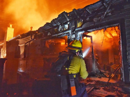 A firefighter battles the flames devouring a home off Fairview Avenue in Goleta.