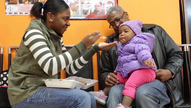 Tierenny Davis, of Rochester, left, feeds daughter N'yliah, 1, during a Thanksgiving meal at Brothers & Sisters Unisex Salon in 2016.